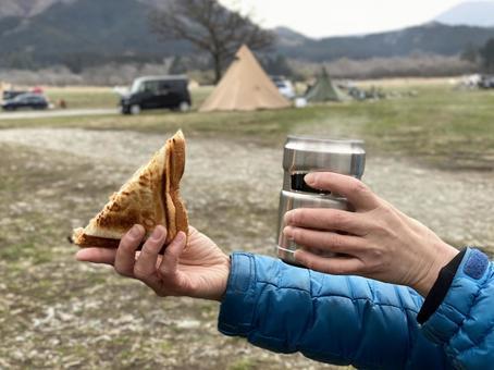 캠프장에서 뜨거운 모래와 스테인레스 컵을 가진 여자의 손