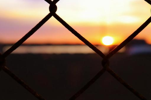 Sunset over the sea seen from the wire mesh