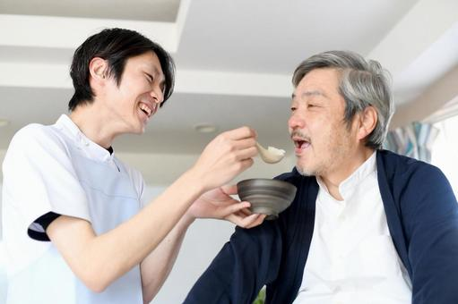 A young man in an apron helping a senior man with a meal