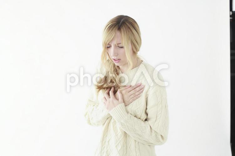 胸を押さえる女性の写真
