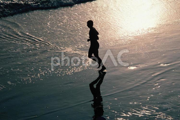 ロスの海辺をジョギングする人の写真