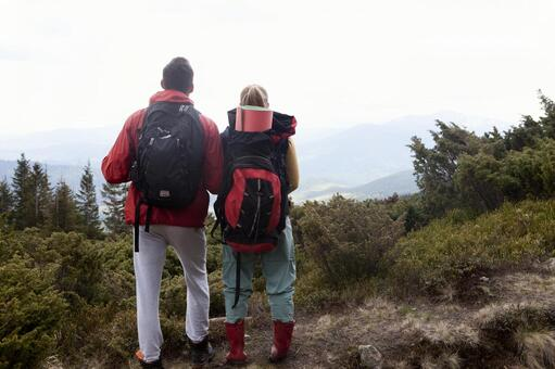 A couple standing and looking at the mountain 1