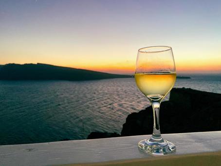 Santorini sea and wine glasses at dusk