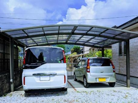 Minivans and light vehicles parked in carports