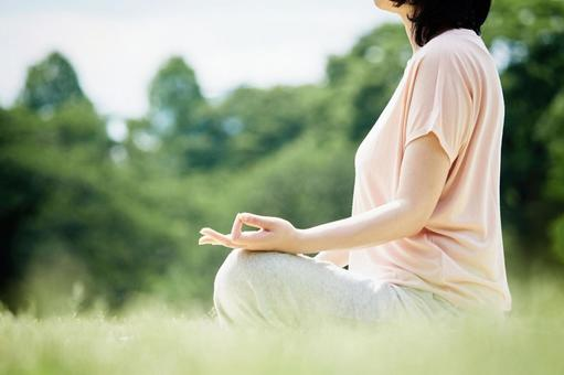 A woman meditating in abundant nature