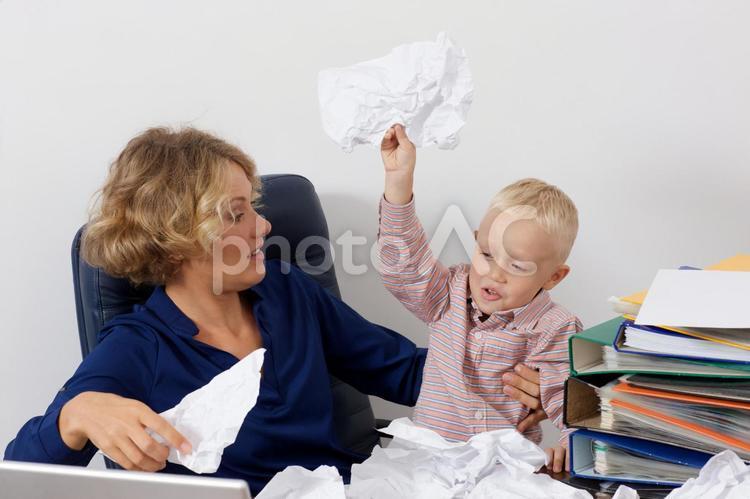 デスクで紙をクシャクシャにする息子を膝に乗せて座るワーキングマザー6の写真