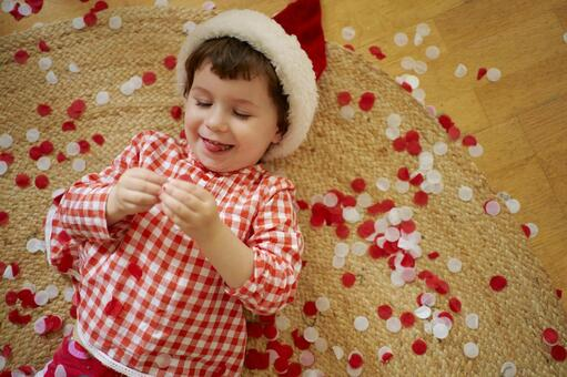 Girl lying on the floor wearing a santa hat