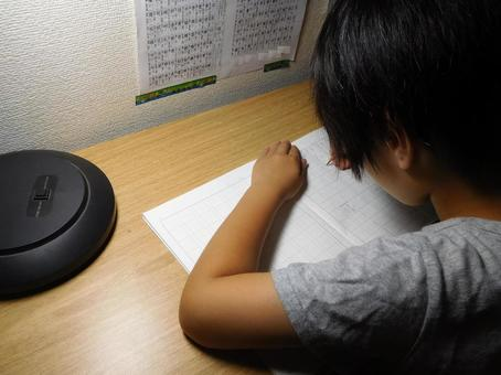 A child (elementary school student) studying kanji at a desk at night