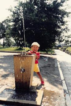 老電影照片男孩在公園的飲水機裡玩耍