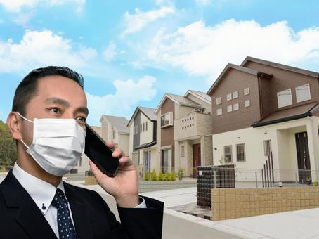 Real estate home sales salesman Corona wearing a mask while using a smartphone to sell a detached house