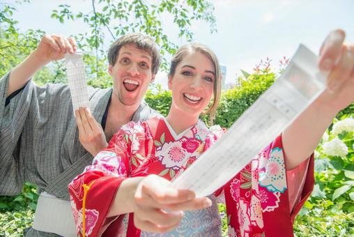 Foreign tourist couple in Yukata with Omikuji in front of hydrangea 1