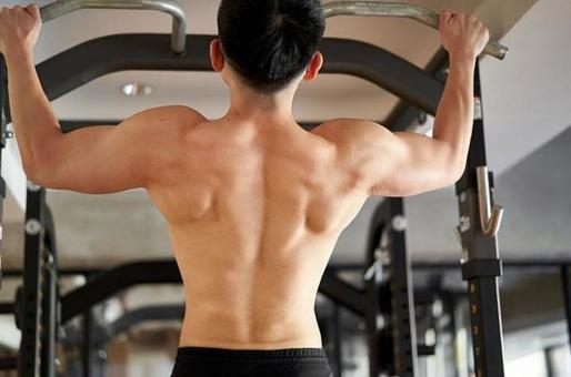 Asian man pulling up in a training gym