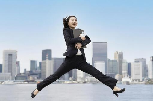 Young business woman / job hunter jumping with a smile
