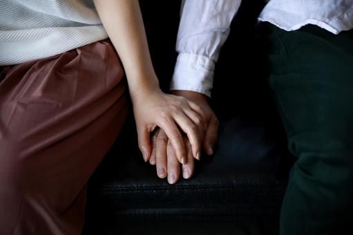 Men and women holding hands on the sofa