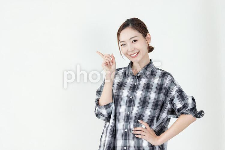 笑顔で指差しポーズをする女性の写真