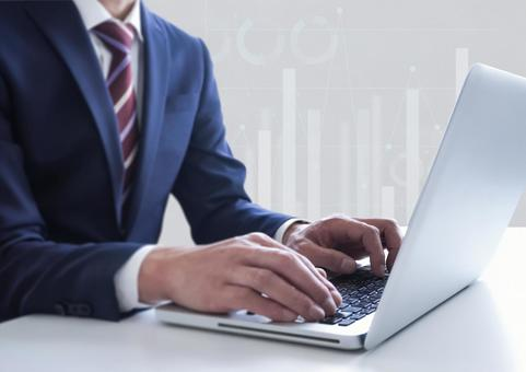 PC operating businessman and graph background