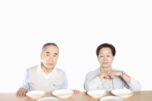 An old couple sitting in front of the table