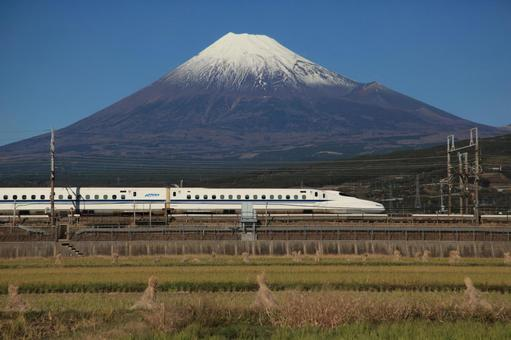 Shinkansen running through the countryside with Mt. Fuji in the background