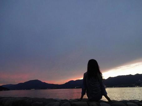 Back view of a woman looking at the Nakaumi at sunset