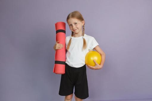 Girl with yoga mat and ball