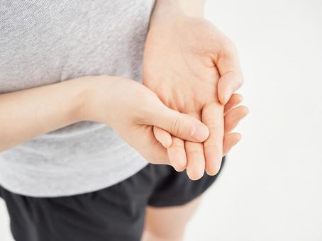 Woman holding a painful finger on a white background