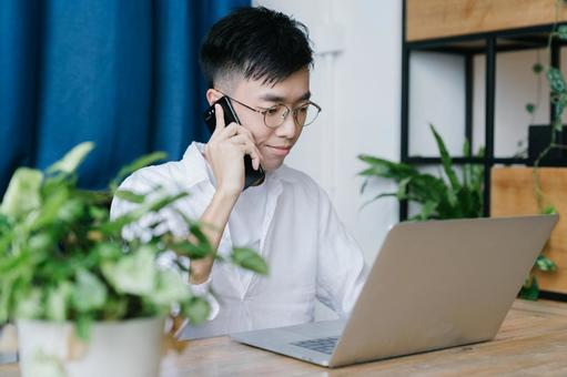 Chinese man using a smartphone at the dining table