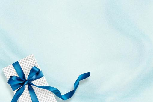 Gift of blue ribbon on light blue drape background