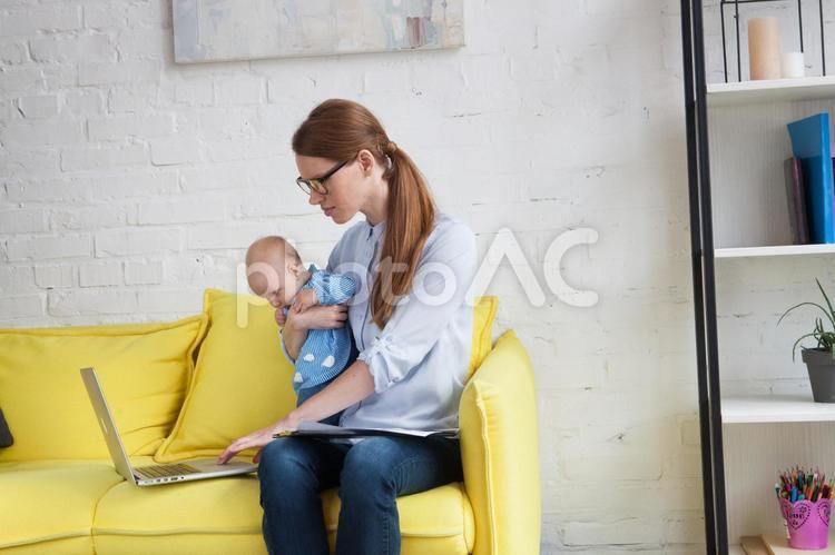 自宅で赤ちゃんを抱っこしながら仕事するお母さん4の写真