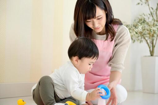 玩具で遊ぶ子供と保育士