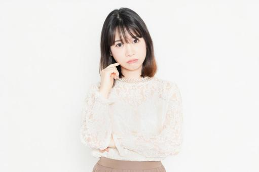 A young woman in a lace blouse, worried, standing in front of a white background