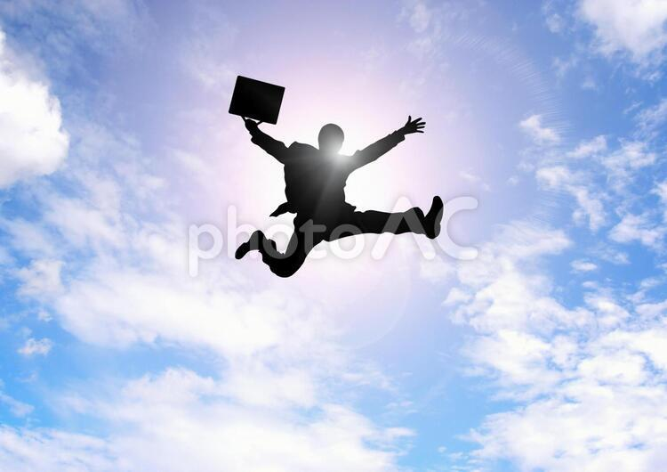 飛躍するビジネスマンの写真