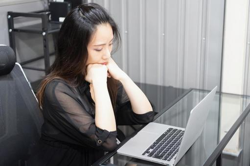 A woman who looks at a computer and thinks