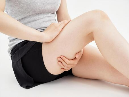 A woman holding a painful thigh on a white background