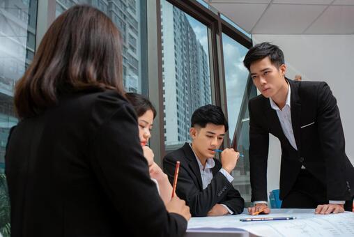 公司員工5在大型圖紙旁開會