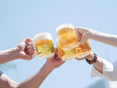 Hands of four men and women toasting with beer under the blue sky