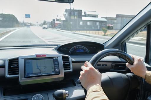 在晴朗的一天駕駛一輛車的男人的手
