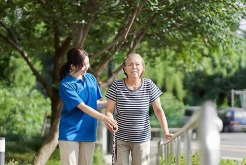 Elderly people walking with the help of a female caregiver