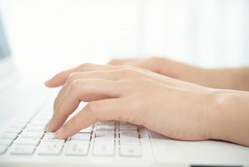 Female hand operating a personal computer