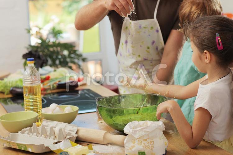 台所で料理の手伝いをする子供たちの写真