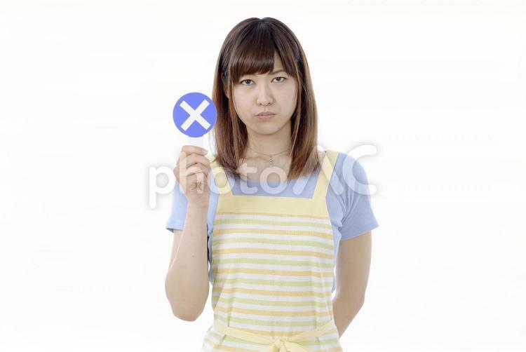 バツの札をあげる女性の写真