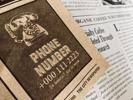 English newspaper layered black telephone