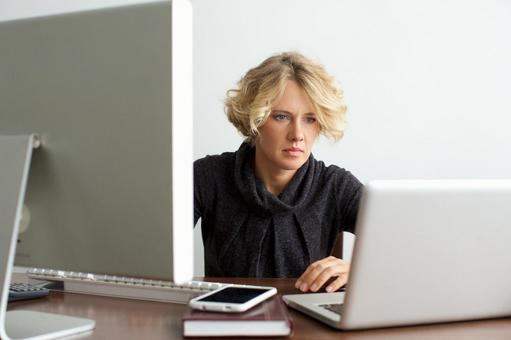 Working mother sandwiched between desktop computer and laptop computer 1