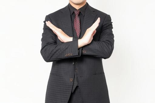 Male businessman standing in front of white background and making NG gestures