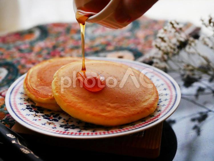 テーブルの上にパンケーキ シロップの写真