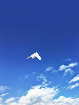 Paper plane flying in the blue sky 1 Vertical
