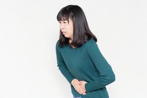 A woman standing in front of a white background and holding her hands on her belly