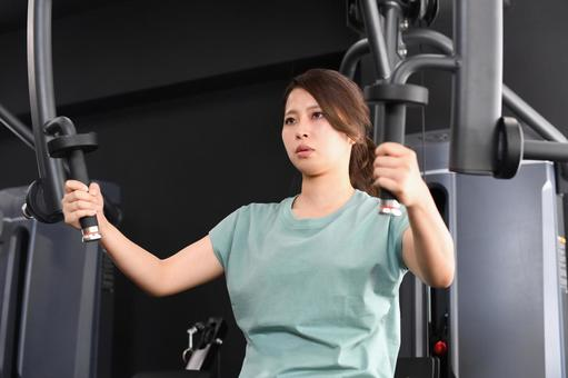 Asian woman doing muscle training (chest press) on a machine