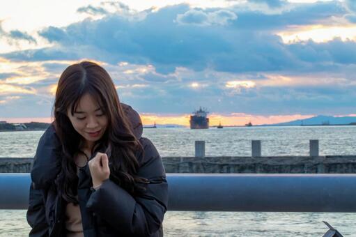 노을 바다를 배경으로 서 여성 인물