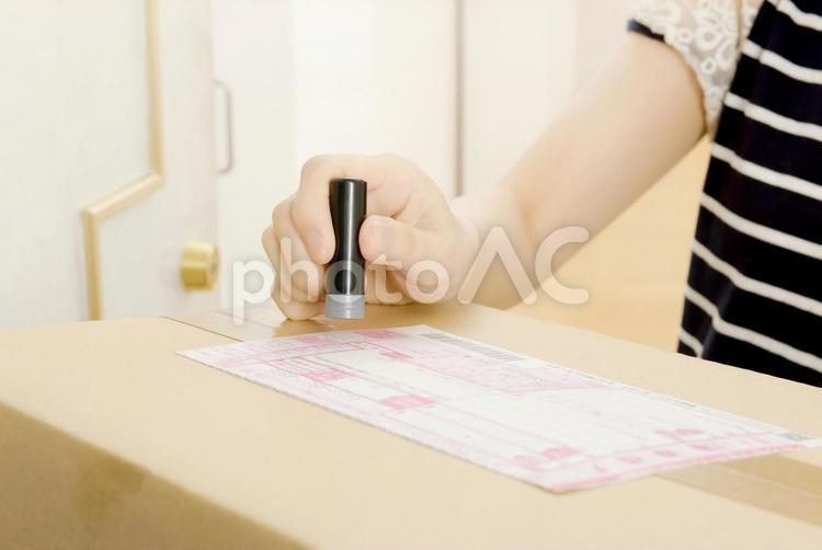 荷物の受取のハンコを押す女性の手元の写真