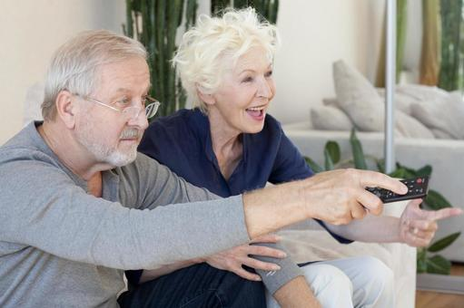 Senior male and female viewing television 4